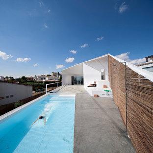 Ejemplo de casa de la piscina y piscina alargada, urbana, de tamaño medio, rectangular, en azotea, con suelo de hormigón estampado