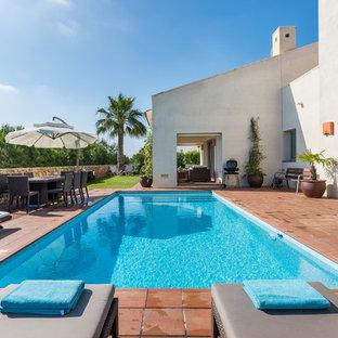 Diseño de piscina alargada, mediterránea, rectangular, en patio trasero, con suelo de baldosas