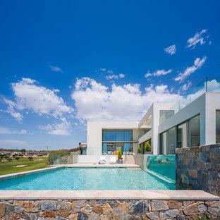 Ejemplo de casa de la piscina y piscina actual, grande, rectangular, en patio lateral
