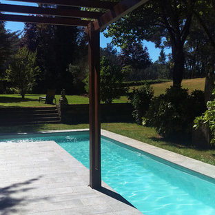 Mid-sized country backyard l-shaped lap pool in Other with a pool house and tile.