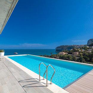 Imagen de piscina con fuente alargada, actual, grande, rectangular, en patio trasero, con entablado
