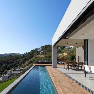 Diseño de piscina alargada, minimalista, pequeña, en forma de L, con entablado
