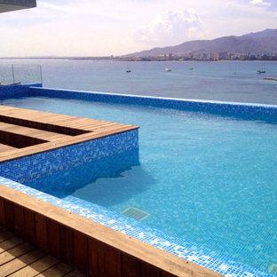 Imagen de casa de la piscina y piscina alargada, contemporánea, de tamaño medio, en forma de L, en azotea, con entablado