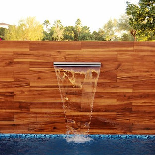 Photo of a small contemporary backyard rectangular lap pool in Other with a water feature.