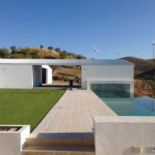 Diseño de piscina infinita, campestre, de tamaño medio, rectangular, en patio lateral, con suelo de baldosas