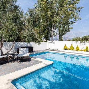 Foto de piscina actual, en forma de L, en patio trasero, con suelo de baldosas