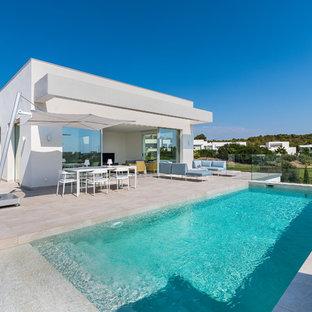 Modelo de piscina moderna, rectangular, en patio trasero, con suelo de baldosas