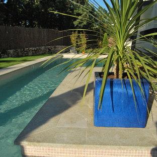 Imagen de piscina alargada, moderna, grande, rectangular, en patio lateral, con gravilla