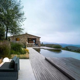 Ejemplo de piscina con fuente infinita, rústica, extra grande, a medida, en patio trasero, con entablado