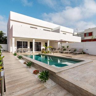 Ejemplo de piscina alargada, contemporánea, rectangular, con suelo de baldosas