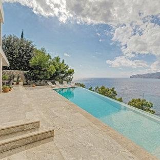 Modelo de casa de la piscina y piscina infinita, mediterránea, de tamaño medio, en patio delantero