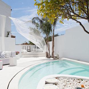 Ejemplo de casa de la piscina y piscina mediterránea, de tamaño medio, a medida, en patio trasero, con losas de hormigón