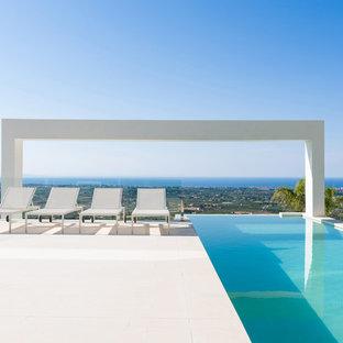 Foto de piscina infinita, moderna, rectangular, en patio trasero, con suelo de baldosas