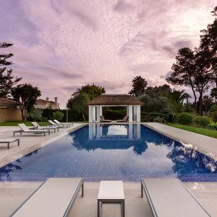 Imagen de casa de la piscina y piscina actual, grande, rectangular, en patio trasero