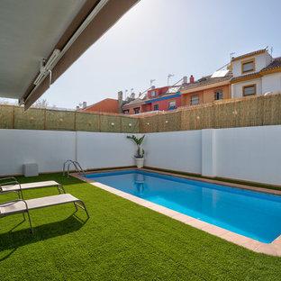Modelo de piscina alargada, mediterránea, rectangular, en patio trasero, con suelo de baldosas