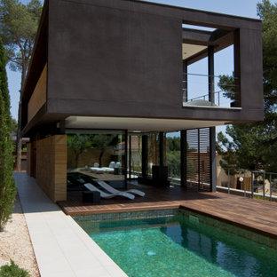 Modelo de piscina actual, de tamaño medio, rectangular, en patio trasero, con suelo de baldosas