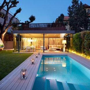 Foto de piscina alargada, contemporánea, grande, rectangular, en patio trasero, con entablado