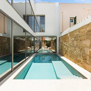 Modelo de piscina alargada, mediterránea, pequeña, rectangular, en patio lateral