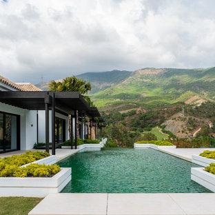 Ejemplo de piscina alargada, mediterránea, a medida, en patio trasero, con losas de hormigón