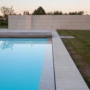 Ejemplo de piscinas y jacuzzis infinitos, minimalistas, de tamaño medio, rectangulares, en patio delantero, con adoquines de piedra natural