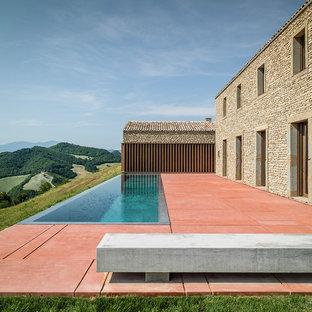 Esempio di una grande piscina a sfioro infinito mediterranea rettangolare dietro casa con una dépendance a bordo piscina e lastre di cemento