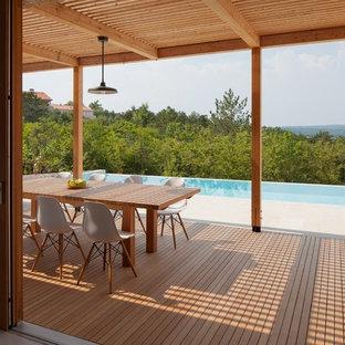 Diseño de piscina infinita, escandinava, grande, rectangular, en patio, con adoquines de hormigón