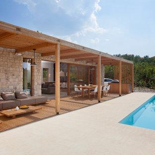 Foto de piscina infinita, nórdica, grande, rectangular, en patio, con adoquines de hormigón