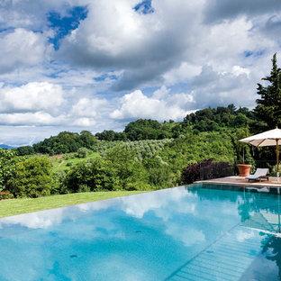 Foto di una piscina a sfioro infinito contemporanea rettangolare dietro casa con pedane