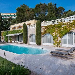 Inspiration pour une très grand piscine arrière méditerranéenne sur mesure avec des pavés en pierre naturelle.