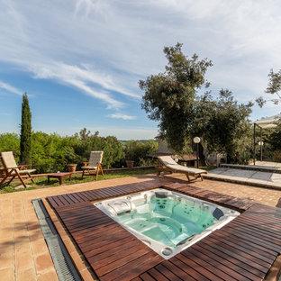 Ispirazione per una piscina country rettangolare dietro casa con una vasca idromassaggio e piastrelle