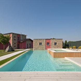 Esempio di una grande piscina country rettangolare dietro casa con una vasca idromassaggio