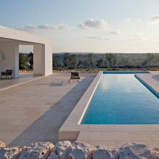 "Immagine di una piscina fuori terra moderna a ""L"" di medie dimensioni e in cortile con pavimentazioni in pietra naturale"