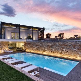 Immagine di una piscina monocorsia design rettangolare di medie dimensioni e dietro casa con pedane