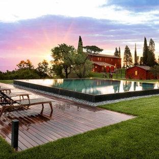 Ejemplo de piscina infinita, ecléctica, grande, a medida, en patio delantero, con adoquines de piedra natural