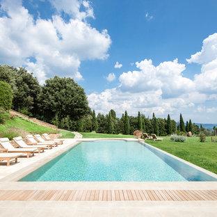 Ispirazione per una piscina monocorsia tradizionale rettangolare dietro casa con pedane