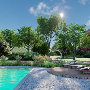 Diseño de piscina alargada, rústica, extra grande, rectangular, en patio delantero, con adoquines de piedra natural
