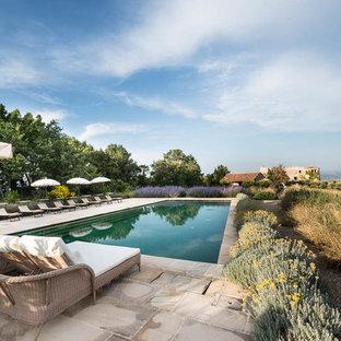 Foto de piscina de estilo de casa de campo, extra grande, rectangular, en patio trasero, con adoquines de piedra natural