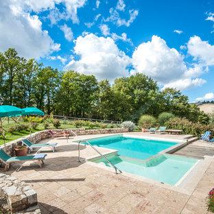 Foto di una piscina mediterranea rettangolare dietro casa con pavimentazioni in pietra naturale e una vasca idromassaggio