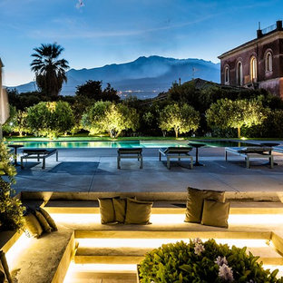 Foto di una grande piscina mediterranea con pavimentazioni in pietra naturale