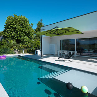 Ispirazione per una piscina a sfioro infinito contemporanea rettangolare di medie dimensioni e dietro casa con pavimentazioni in pietra naturale