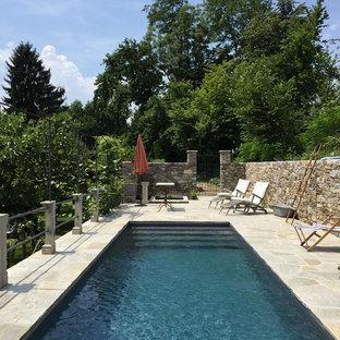 Immagine di una piscina monocorsia mediterranea rettangolare dietro casa con piastrelle