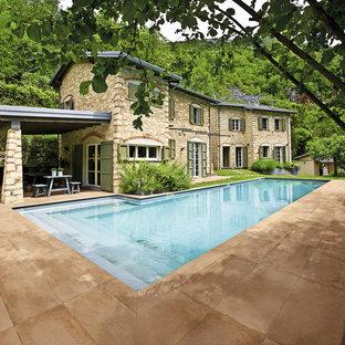 """Foto di una grande piscina monocorsia mediterranea a """"L"""" nel cortile laterale con una dépendance a bordo piscina e piastrelle"""