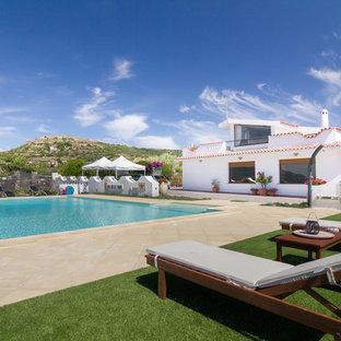 Esempio di una grande piscina mediterranea rettangolare nel cortile laterale con pavimentazioni in pietra naturale