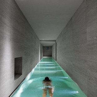 Esempio di una piscina coperta moderna rettangolare di medie dimensioni con pavimentazioni in pietra naturale