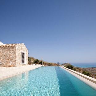 """Idee per una piscina a sfioro infinito mediterranea a """"L"""" dietro casa con pavimentazioni in pietra naturale"""