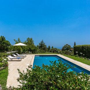 Immagine di una grande piscina country rettangolare con pavimentazioni in pietra naturale