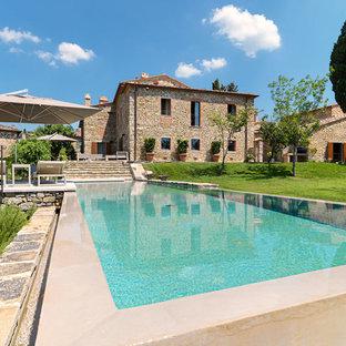 Diseño de piscina elevada, de estilo de casa de campo, grande, rectangular, en patio delantero, con adoquines de hormigón