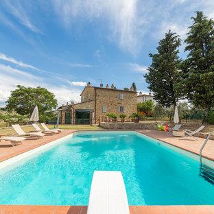 Foto di una grande piscina monocorsia country rettangolare nel cortile laterale con una dépendance a bordo piscina e piastrelle