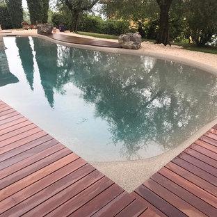 Ejemplo de piscina natural, mediterránea, de tamaño medio, a medida, en patio delantero, con entablado