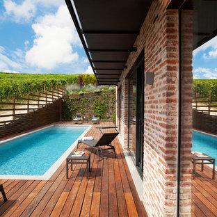 Ejemplo de piscina alargada, campestre, rectangular, en patio trasero, con entablado